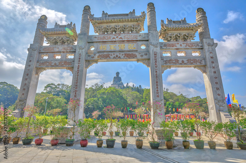Scenic gateway in a sunny day of Po Lin Monastery and the Big Buddha on background, icon and symbol of Lantau Island, popular tourist destination of Hong Kong, China.