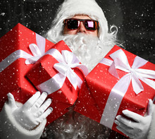Santa Claus With Red Presents Gifts For New Year And Sunglasses Standing Under Snow