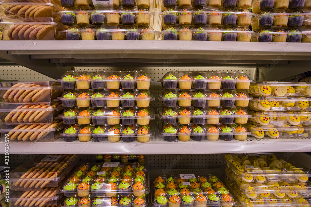 Fototapety, obrazy: holiday cookies and cupcakes on a shelf in a store in different colors