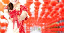 Happy Chinese New Year. Asian Woman Holding Gift Box. Copy Space  And Red Lanterns Blur Background