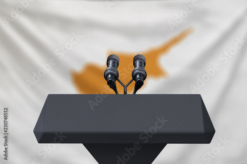 Podium lectern with two microphones and Cyprus flag in background