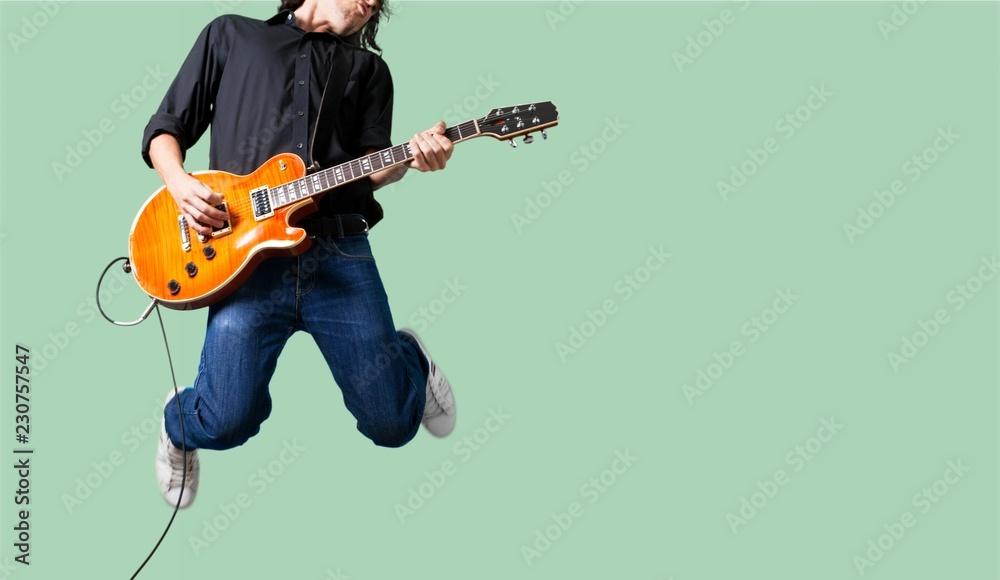 Male Guitarist playing music on grey wall