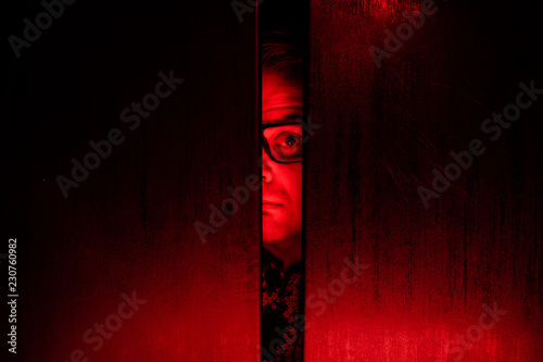 Photo Agoraphobia concept / eye peeking behind the door