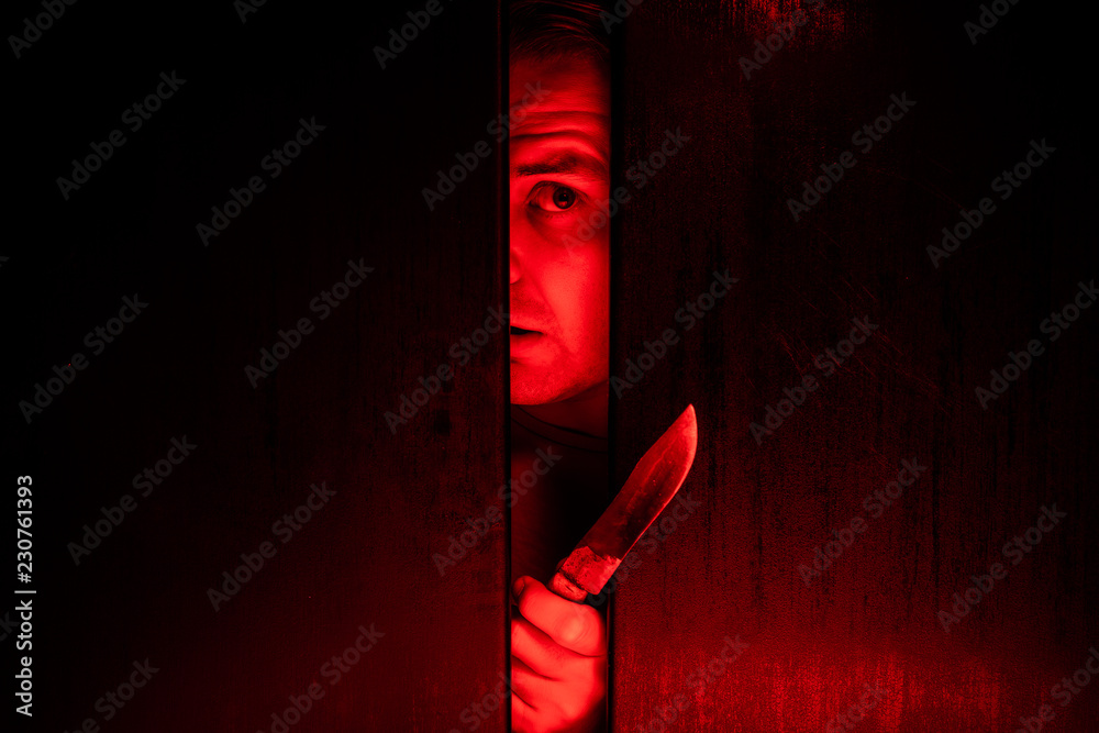 Fototapeta Serial killer / eye peeking behind the door with kinfe