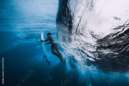 Photo Professional surfer with surfboard dive underwater