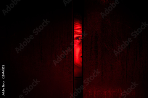 Agoraphobia concept / eye peeking behind the door Canvas Print