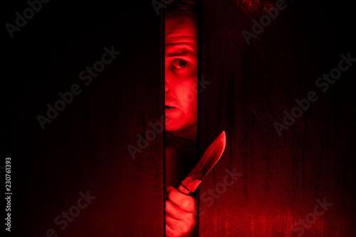 Serial killer / eye peeking behind the door with kinfe Wallpaper Mural