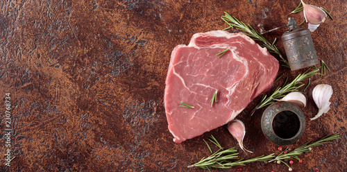 Raw beef steak with spices and herbs.