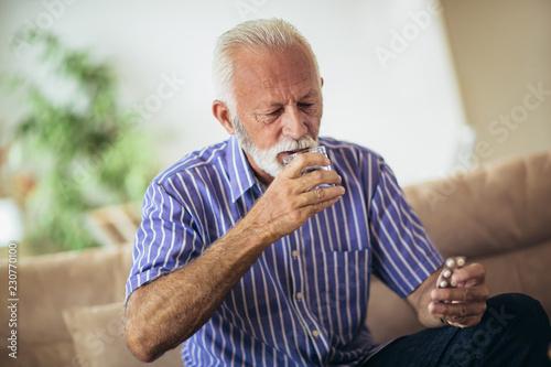Fototapeta Senior man taking pills at home obraz