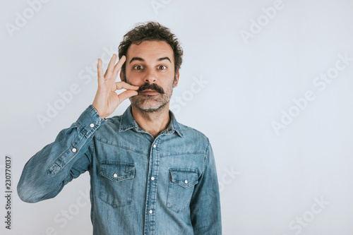 Photo Funny portrait of brown, smiling, handsome man touching his mustache