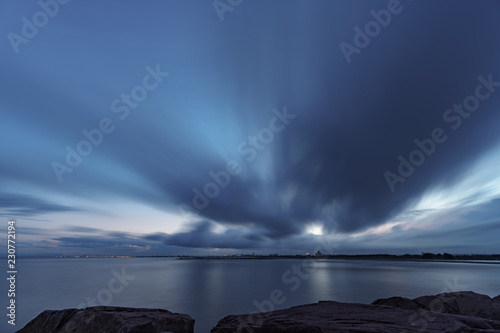 Fotografie, Obraz  Long exposure at sunset from breakwater with ocean and coastal city