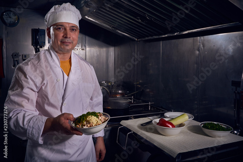 chef cook in a white apron and cooks hat on a kitchen doing his lovely job Slika na platnu
