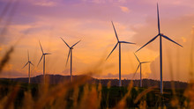Wind Turbines Produce Electricity And Sunlight During Sunset.