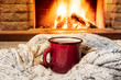 canvas print picture - Cozy scene near fireplace with a Red enameled mug with hot tea and cozy warm scarf.