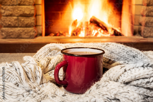 Vászonkép Cozy scene near fireplace with a Red enameled mug with hot tea and cozy warm scarf