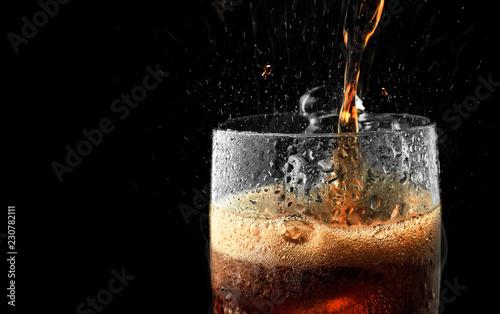 Fotografía  Soft drink glass with ice splash on dark background