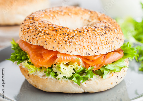 Fresh healthy bagel sandwich with salmon, ricotta and lettuce in grey plate on light kitchen table background. Healthy diet food. Glass of milk and fresh vegetables