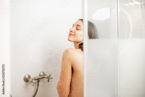 Tableau sur Toile Young and beautiful woman washing her face, taking a shower in the white cabin