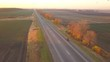 Aerial: motorbike on the asphalt road at sunset time