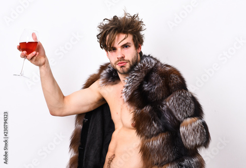 Guy attractive rich posing fur coat on naked body. Rich athlete enjoy his life. Fashion and pathos. Richness and luxury concept. Sexy sleepy rich macho tousled hair drink wine isolated on white