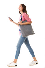 Side Portrait Of Fashionable Young Asian Woman Walking With Purse And Smart Phone Against Isolated White Background
