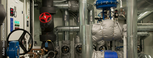 Photo Equipment, cables, pipes and valves in engine room of a ship power plant