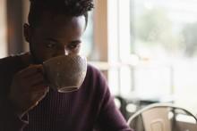 Man Having Coffee In Cafe