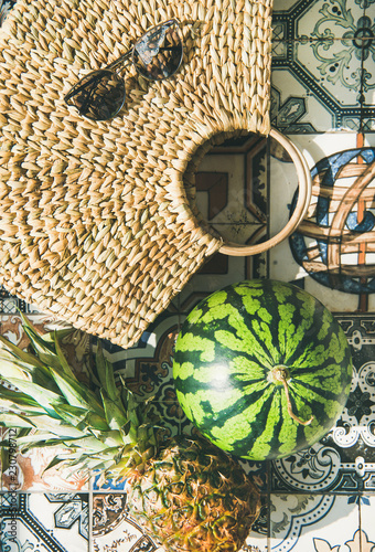 Summer lifestyle background. Flat-lay of summer fruit pineapple and watermelon, straw bag and sunglasses over colorful moroccan tile floor, top view