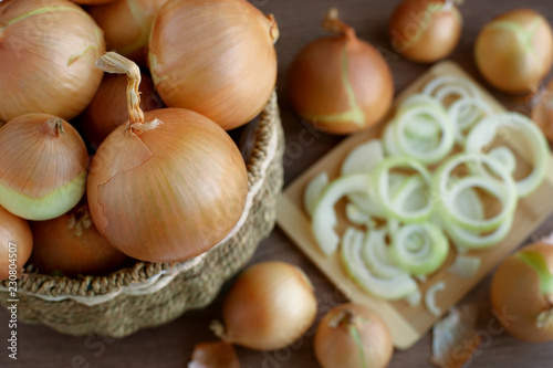 A lot of onions in a wicker basket on top of sight. Harvest onions in a wicker basket and cooking vegetables. Sliced onions on a cutting board.