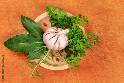 An overhead photo of garlic, aromatic kitchen herbs and spices, shot from above in a wooden bowl on a rustic cutting board background with a place for text