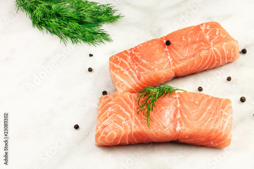 A photo of two slices of salmon on a white marble kitchen table with salt, pepper, and dill, with a place for text