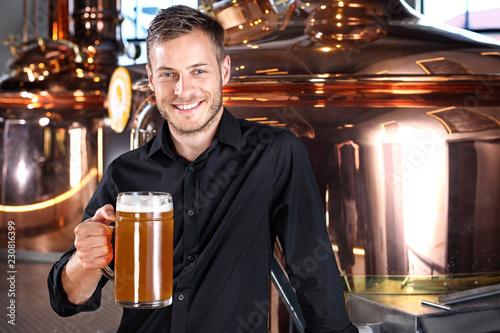 Piwo kuflowe. Uśmiechnięty przystojny mężczyzna z kuflem piwa pszenicznego.