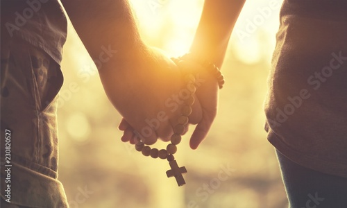 Fotografía Couple praying together. Holding rosary in hand.