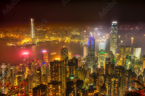 Aerial view of Victoria Harbour skyline by night from Lugard Road Lookout at Victoria Peak, the highest mountain in Hong Kong Island. Business skyscrapers with their lights and neon.