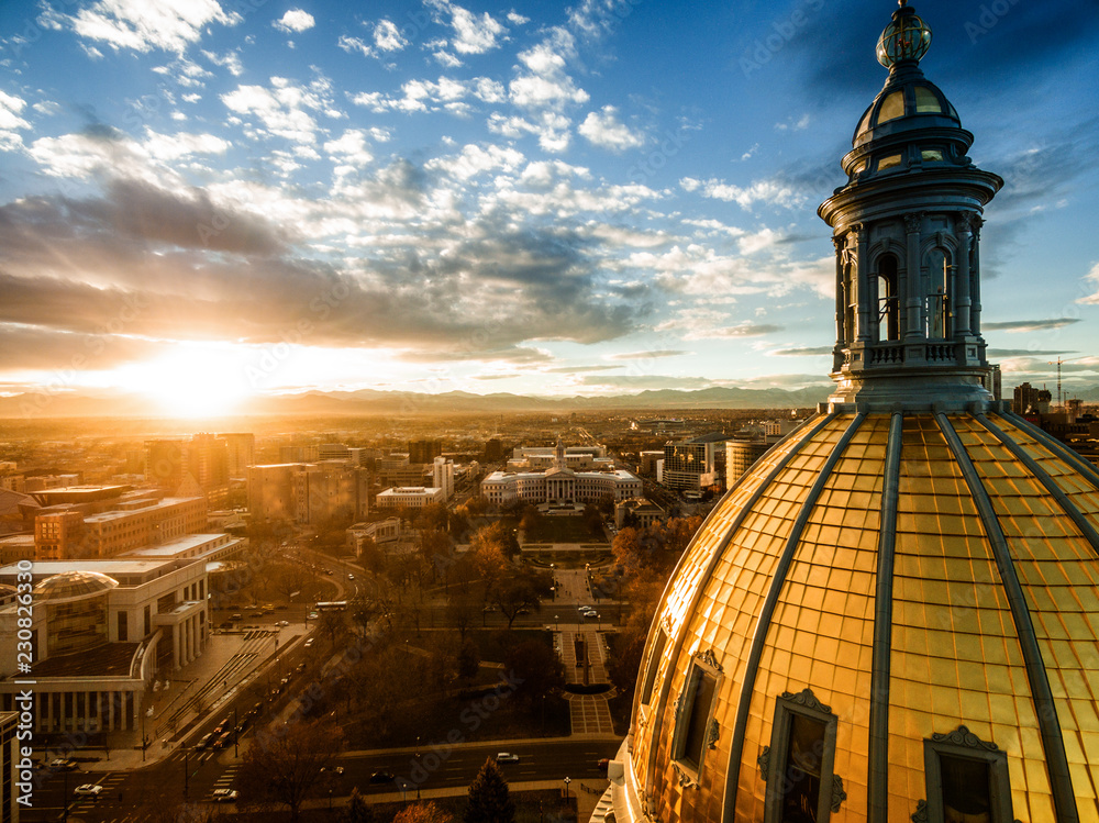 Fototapety, obrazy: Aerial/Drone photograph of a sunset over the Colorado state capital building.  Capital city of Denver.  The Rocky Mountains can be seen on the horizon