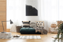 Poster Above Green Futon With Patterned Pillows In Bright Living Room Interior With Lamp. Real Photo