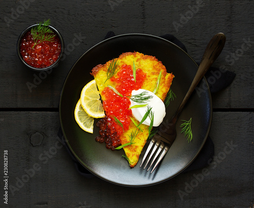 Potato rusty (potato pancake) with red caviar. View from above.