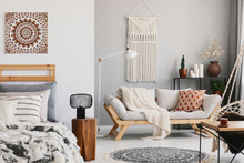 Small Open Space Flat Interior With Beige Sofa With Cushion, Macrame On The Wall, Rack With Candles And Plants And Bed With Pillows