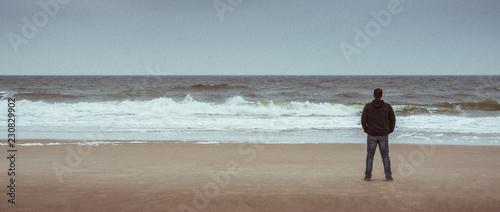 Photo Mann steht allein am Strand und schaut auf das weite Meer