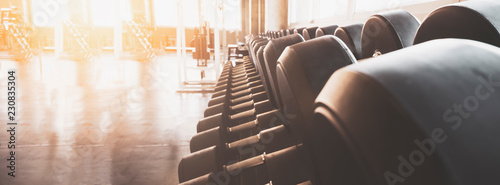 Fotografia Gym equipment wide interior gym for fitness banner background close up dumbbells