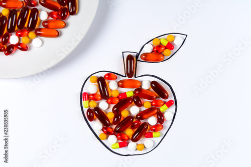 Valokuva  Hand holding drawing apple with colorful capsules and pills on white background