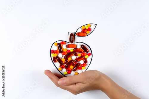Hand holding drawing apple with colorful capsules and pills on white background Canvas-taulu