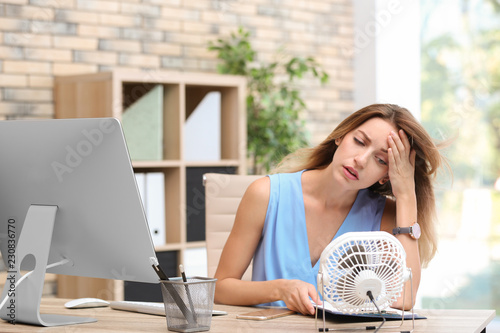 Photographie Businesswoman suffering from heat in front of small fan at workplace