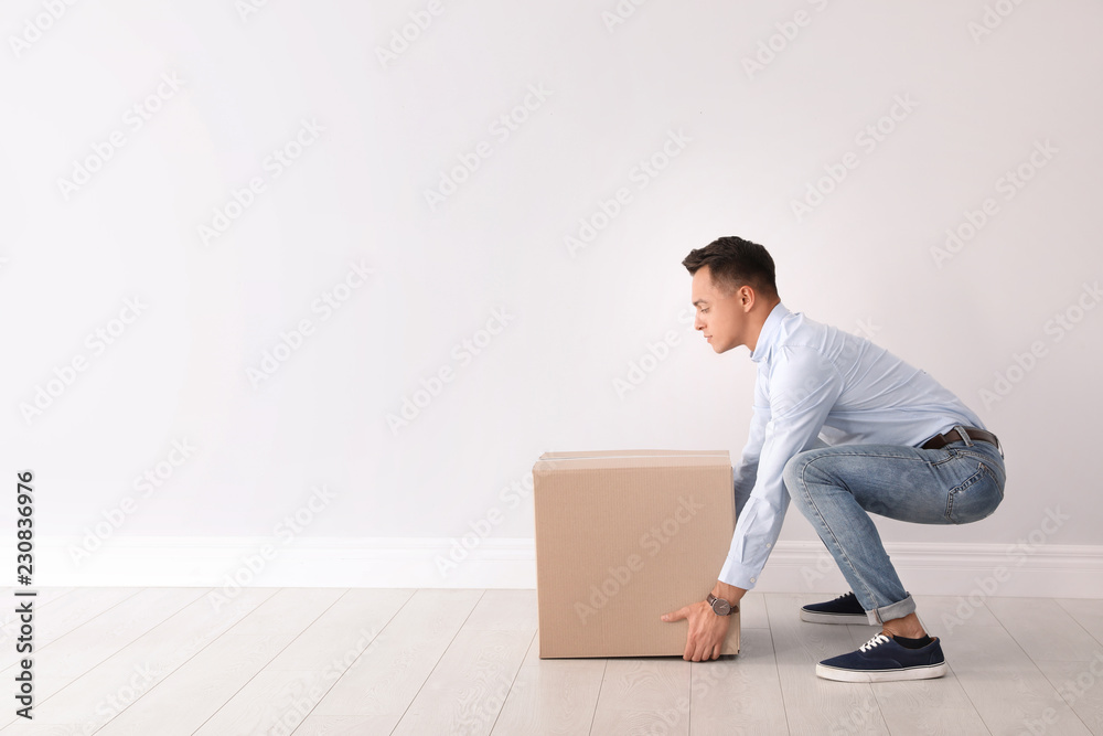 Fototapety, obrazy: Full length portrait of young man lifting heavy cardboard box near white wall. Posture concept