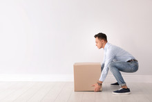 Full Length Portrait Of Young Man Lifting Heavy Cardboard Box Near White Wall. Posture Concept