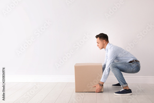 Cuadros en Lienzo  Full length portrait of young man lifting heavy cardboard box near white wall