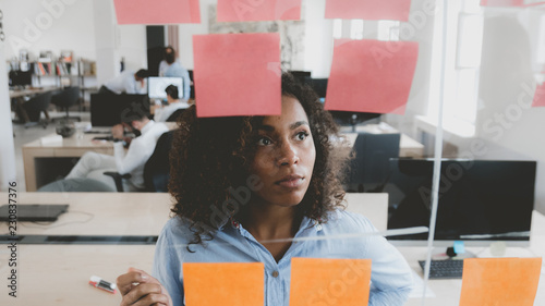 Photo African American black employee looking onto a glass wall with sticky notes, fra
