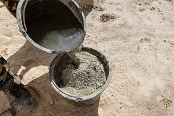 Fototapeta Mixing of concrete in a bucket at a construction site