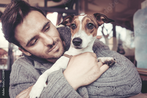 Fotografía  Man cuddling with his terrier dog in winter