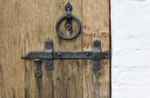 Old Wooden Door With Wrought Iron Latch And Handle In The Form Of A Ring And A White Stone Wall